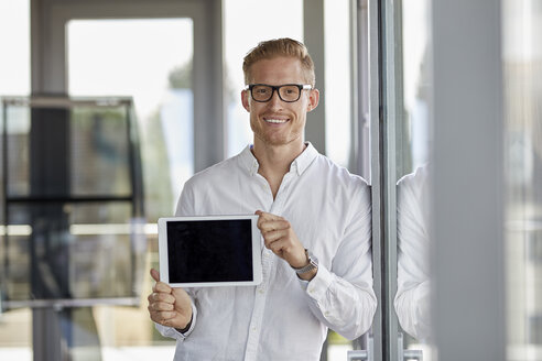 Portrait of smiling businessman showing tablet at the window in office - RBF06719