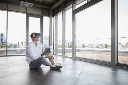 Businessman sitting in empty room wearing VR glasses - RBF06722