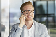Portrait of smiling redheaded businessman on cell phone - RBF06728