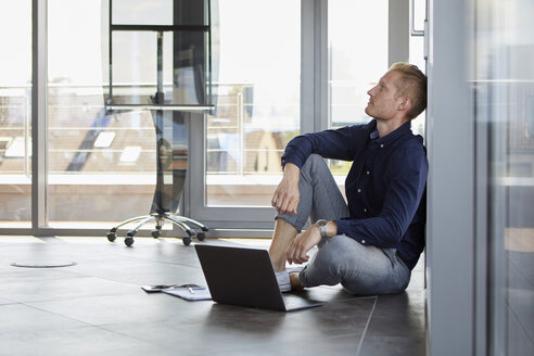 Businessman sitting on the floor next to laptop - RBF06731