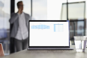 Chart on laptop screen on desk in office with businessman in background - RBF06743