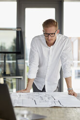 Young man working on blueprint on desk in office - RBF06749