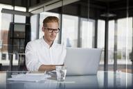 Businessman using laptop on desk in office - RBF06752