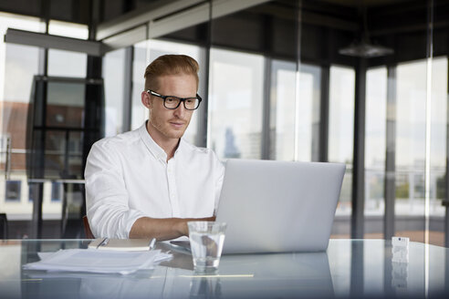 Businessman using laptop on desk in office - RBF06752