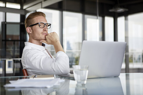 Businessman with laptop on desk in office thinking - RBF06755