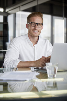 Portrait of smiling businessman using laptop on desk in office - RBF06758