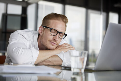 Businessman leaning on desk in office with closed eyes - RBF06761