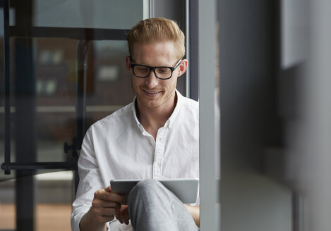 Smiling businessman sitting on windowsill using tablet - RBF06767