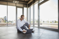 Businessman sitting in empty room with panorama window using laptop - RBF06773