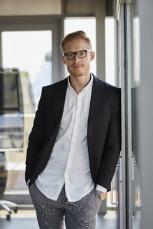 Portrait of confident businessman in office leaning against window - RBF06779