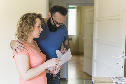 Couple examining contract of new home - FBAF00039