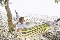 Croatia, Cres Island, man with laptop lying in hammock on a beach looking at distance - JESF00161