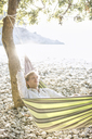 Croatia, Cres Island, man relaxing in hammock on the beach - JESF00164