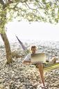 Man lying in hammock on a beach using laptop - JESF00170