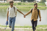 Portrait of young gay couple with backpacks walking hand in hand at riverside - FBAF00050