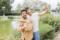 Portrait of young gay couple taking selfie with smartphone at city park - FBAF00056