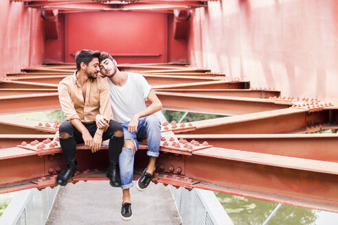 Young gay couple in love sitting on steel girder of a footbridge - FBAF00074