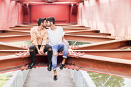 Kissing young gay couple sitting on steel girder of a footbridge - FBAF00077