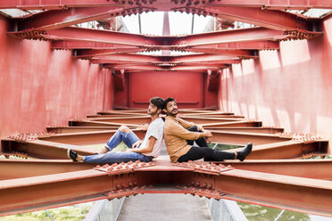 Young gay couple sitting back to back on steel girder of a footbridge - FBAF00080