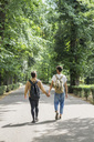 Back view of young gay couple with backpacks walking hand in hand on a road - FBAF00083