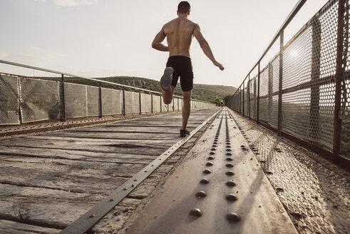 Rear view of young shirtless man running on bridge - JASF01958