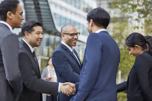 Businesspeople greeting each other at business park - LUXF00197