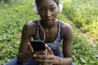 Young athlete in nature, listening music with headphones, holding smartphone - GIOF04449