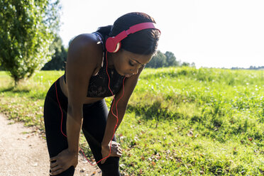 Young athlete in nature, listening music with headphones, preparing for training - GIOF04455