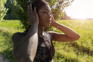Young athlete in nature, listening music with headphones, preparing for training - GIOF04467