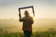 Italy, Tuscany, Borgo San Lorenzo, senior man holding window frame in field at sunrise above rural landscape - FBAF00092