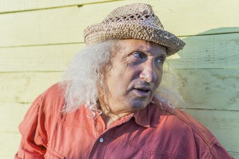 Senior man with long gray hair wearing straw hat looking sideways - FBAF00104