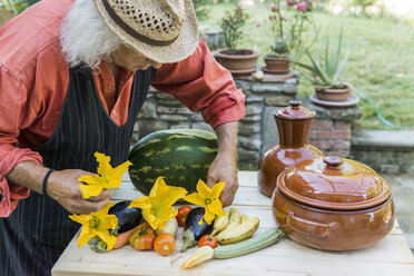 Senior man decorating a table with fruits and vegetables - FBAF00107
