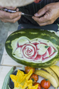 Close-up of man decorating a watermelon with carving tool - FBAF00110
