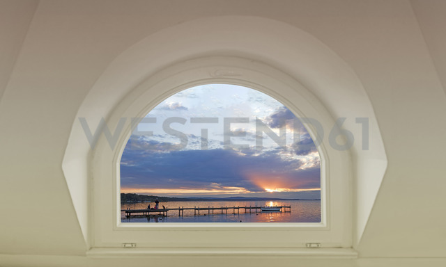 Germany, Lower Saxony, view to jetty and boat at sunset from inside - KLR00706
