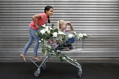 Two girls playing with shopping cart decorated with artificial flowers - PSTF00174
