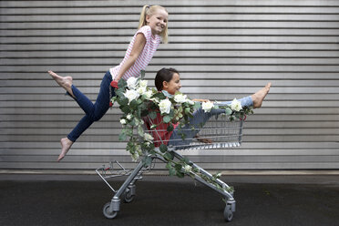 Two happy girls playing with shopping cart decorated with white artificial flowers - PSTF00177