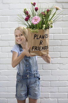 Portrait of smiling girl holding paper bag with flowers - PSTF00183