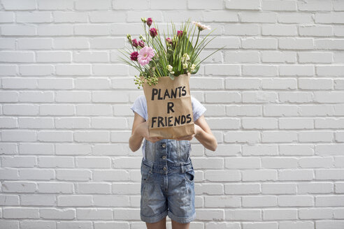 Girl hiding behind paper bag with flowers - PSTF00186