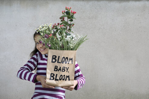 Smiling girl holding paper bag with flowers - PSTF00189