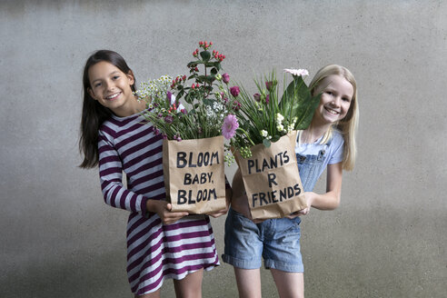 Portrait of two smiling girls holding paper bags with flowers - PSTF00195