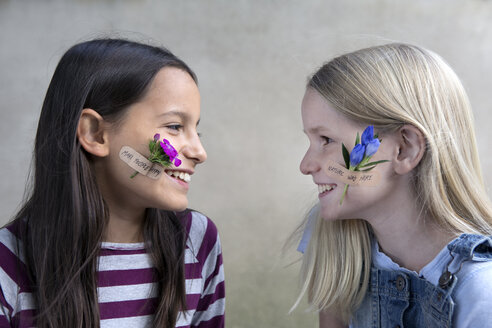 Two smiling girls with flower heads on their cheeks - PSTF00201