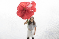 Portrait of smiling girl standing in a lake holding oversized red artificial flower - PSTF00204