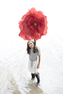Portrait of smiling girl standing in a lake with oversized red artificial flower - PSTF00207