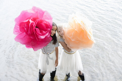Two girls standing in a lake with two oversized artificial flowers - PSTF00210