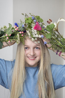 Portrait of smiling blond girl with bunches of flowers - PSTF00216