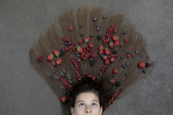 Portrait of girl lying on floor with fruits on hair looking up - PSTF00219