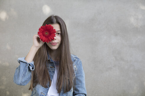 Portrait of smiling girl with flower head of red Gerbera - PSTF00234