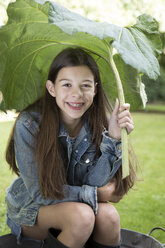 Portrait of smiling girl under big leaf sitting in tub in the garden - PSTF00237