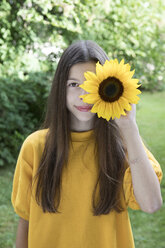 Portrait of smiling girl with sunflower in the garden - PSTF00240