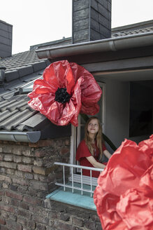 Smiling girl with oversized redc artifical flower looking out of window - PSTF00246